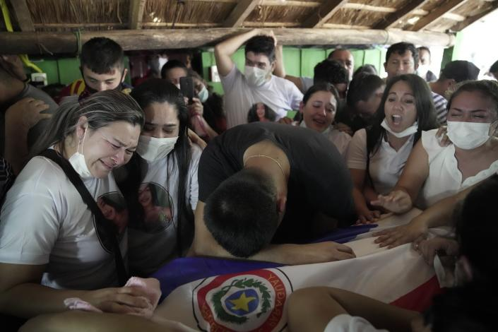 Relatives of Leidy Vanessa Luna Villalba mourn over the flag-draped coffin that contain her remains in her hometown of Eugenio Garay, Paraguay, Tuesday, July 13, 2021. Luna Villalba, a nanny employed by the sister of Paraguay's first lady Silvana Lopez Moreira, was among those who died in the Champlain Towers South condominium collapse in Surfside, Florida on June 24. (AP Photo/Jorge Saenz)