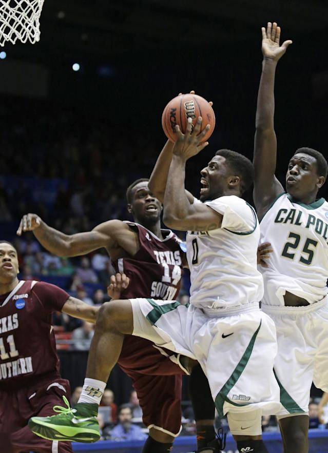 Cal Poly guard Dave Nwaba (0) drives against Texas Southern guard Ray Penn Jr. (14) in the first half of a first-round game of the NCAA college basketball tournament on Wednesday, March 19, 2014, in Dayton, Ohio. Cal Poly forward Joel Awich (25) and Texas Southern guard Lawrence Johnson-Danner (11) watch. (AP Photo/Al Behrman)