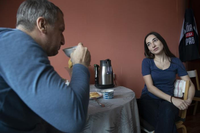 In this photo taken on Saturday, May 16, 2020, Dr. Osman Osmanov drinks coffee with his wife Saida at home after his shift at an intensive care unit of Filatov City Clinical Hospital in Moscow, Russia. Moscow accounts for about half of all of Russia's coronavirus cases, a deluge that strains the city's hospitals and has forced Osmanov to to work every day for the past two months, sometimes for 24 hours in a row. (AP Photo/Pavel Golovkin)