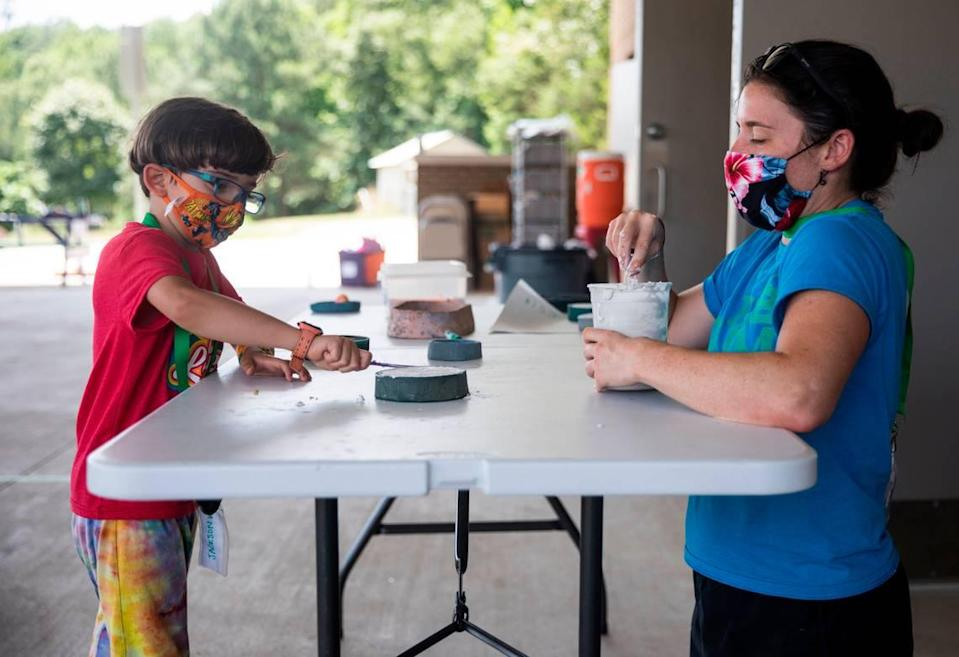 Erin Hoerner, right, who teaches special education at Glenn Elementary School during the school year, helps Jackson Wilfong, 6, make a plaster mold at The Hub Farm, an outdoor learning center in Durham, N.C., on Monday, June 21, 2021. At The Hub Farm, next door to Eno Valley Elementary School, students who did not struggle academically during the school year participate in outdoor learning activities.