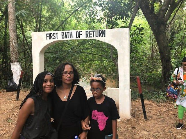 Dr. Lesley Hanes stands outside the Assin Manso Last Bath Slave River with her daughters, Jasmine, 14, (left) and Maya, 10. The river is where captured Africans were taken for their last bath before being shipped to the western world.