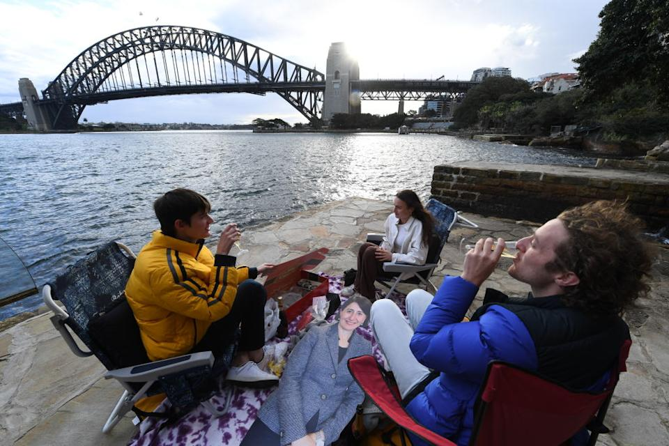 Patrick Slocombe, Max Mazaraki and Rosie O'Shea gather together at Mary Booth Lookout Reserve in Kirribilli for a champagne and oyster picnic alongside a life sized cardboard cutout of the Premier of New South Wales, Gladys Berejiklian in Sydney, Australia.