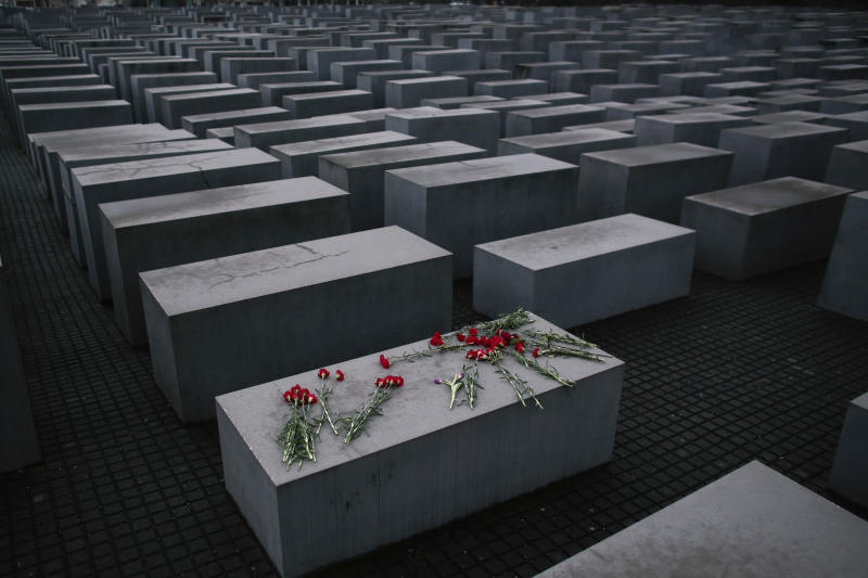 In this Tuesday, Jan. 27, 2015 file photo, flowers lay on a concrete slab of the Holocaust Memorial to mark the International Holocaust Remembrance Day in Berlin. One of Germany's richest families, the Reimann family, which owns Krispy Kreme Doughnuts, Pret A Manger, Peet's Coffee and other famous international brands is giving millions to support Holocaust survivors. The family has established the Alfred Landecker Foundation in Germany to oversee the efforts, named after a German Jew who was killed by the Nazis either in Sobibor or at the Belzec Nazi death camp.(AP Photo/Markus Schreiber, file)
