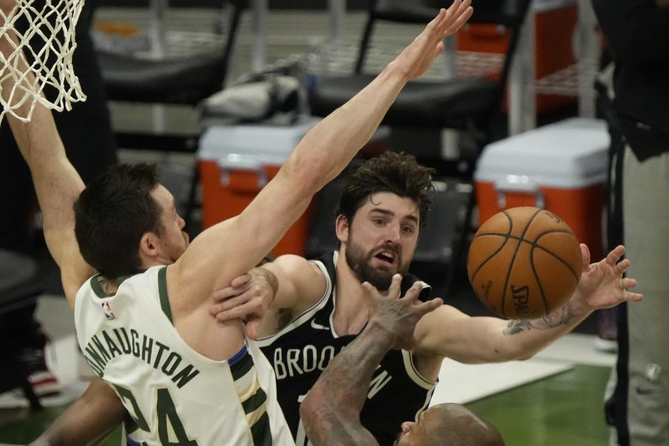 Milwaukee Bucks' Pat Connaughton knocks the ball from Brooklyn Nets' Joe Harris during the first half of Game 4 of the NBA Eastern Conference basketball semifinals game Sunday, June 13, 2021, in Milwaukee. (AP Photo/Morry Gash)