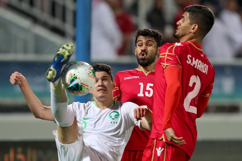 FIFA suspended Bahrain defender Sayed Baqer (right) 10 games for making a racist gesture. (Karim Jaafar/AFP/Getty Images)