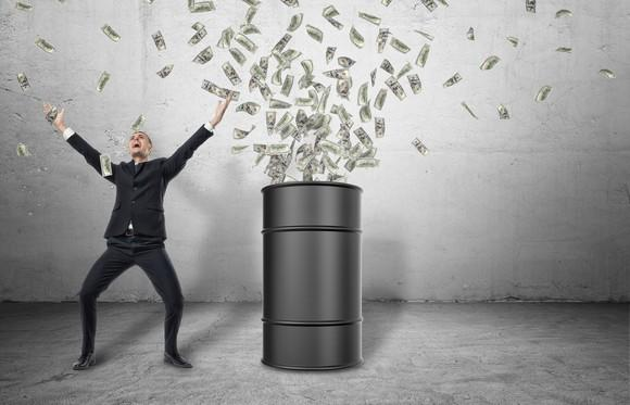 A smiling man stands next to an oil barrel emitting a cloud of paper money
