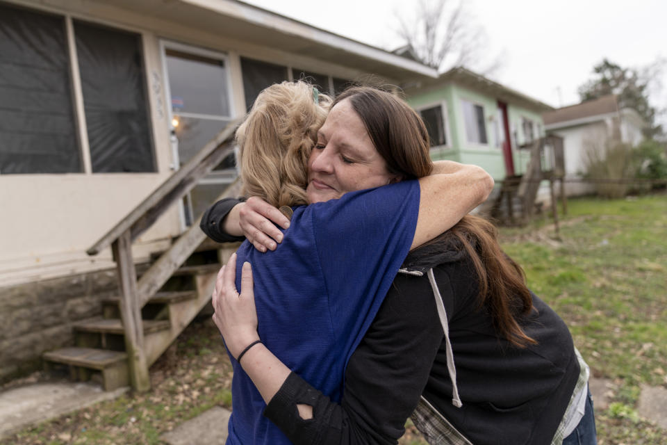 """Sarah Kelly, right, is embraced by Sue Howland, with the Quick Response Team, after Howland presented her with a coin marking Kelly's one-year anniversary in recovery, outside her home in Guyandotte, W.Va., Wednesday, March 17, 2021. After struggling with opioid addiction most of her life, Kelly white-knuckled her way through the pandemic. """"I didn't know where to stop and pick up the pieces. It felt like the task was too overwhelming to get out of the mess I made,"""" she said. """"How do you come back from this?"""" But she did, and it feels to her like a miracle. (AP Photo/David Goldman)"""