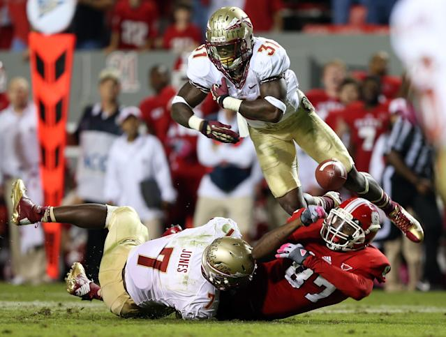 RALEIGH, NC - OCTOBER 06: Teammates Terrence Brooks #31 of the Florida State Seminoles and Christian Jones #7 collide with Mario Carter #87 of the North Carolina State Wolfpack during their game at Carter-Finley Stadium on October 6, 2012 in Raleigh, North Carolina. (Photo by Streeter Lecka/Getty Images)