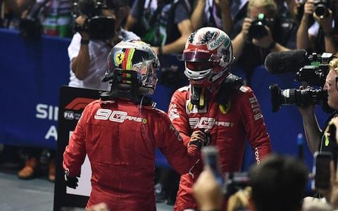 Ferrari's German driver Sebastian Vettel (L) celebrates with Ferrari's Monegasque driver Charles Leclerc (R) after Vettel's victory in the Formula One Singapore Grand Prix night race at the Marina Bay Street Circuit in Singapore on September 22, 2019