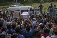 Kashmiri men carry the coffin of Waseem Ahmed, a policeman who was killed in a shootout, out of an ambulance on the outskirts of Srinagar, Indian controlled Kashmir, Sunday, June 13, 2021. Two civilians and two police officials were killed in an armed clash in Indian-controlled Kashmir on Saturday, police said, triggering anti-India protests who accused the police of targeting the civilians. (AP Photo/ Dar Yasin)