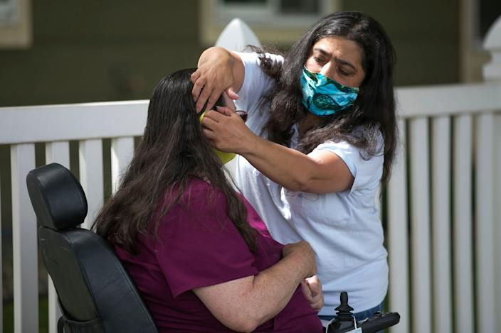 Lupe Anderson helps Christine Laframboise put on a mask on July 9, 2020, in Yakima, Washington.