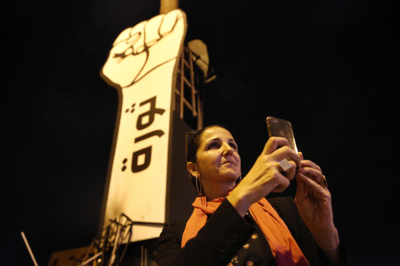 In this Friday, Nov. 8, 2019 photo Singer Tania Saleh takes pictures by her mobile phone at the martyrs square where the ongoing anti-government take place everyday, in downtown Beirut, Lebanon. Saleh grew up amid a civil war that has robbed her of her childhood. Of her friends and neighbors. And of the Lebanon she so loved.   (AP Photo/Hussein Malla)