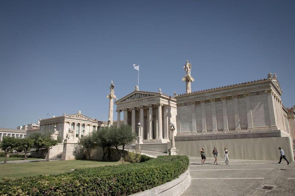 """<p>The main building of the Academy of Athens was designed as part of an architectural """"trilogy"""" in 1859 by the Danish architect Theophil Hansen, along with the University and the National Library. Construction began in 1859 but the building was not completed until 1885. Greek sculptor Leonidas Drosis sculpted the multi-figure pediment sculptire and the figures of Athena and Apollo on the pair of pillars flanking the Academy's portico.</p>"""