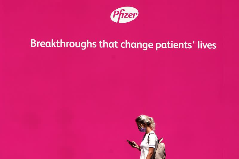 FILE PHOTO: A woman walks past a sign outside Pfizer Headquarters in the Manhattan borough of New York City