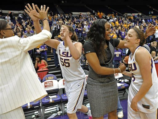 LSU coach Nikki Caldwell, left, high-fives Theresa Plaisance (55) as assistant coach Tasha Butts, second from right, celebrates the win with LSU guard Jeanne Kenney after an NCAA college basketball game in Baton Rouge, La., Sunday, Feb. 24, 2013. LSU defeated Kentucky 77-72. (AP Photo/Bill Feig)