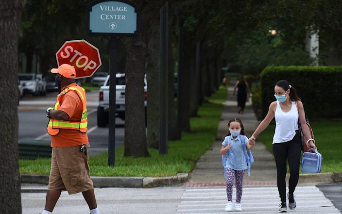"A mother walks her child to school on the first day of in-person classes in Orange County at Baldwin Park Elementary School on August 21, 2020 in Orlando, Florida. <p class=""copyright"">Paul Hennessy/NurPhoto via Getty Images</p>"