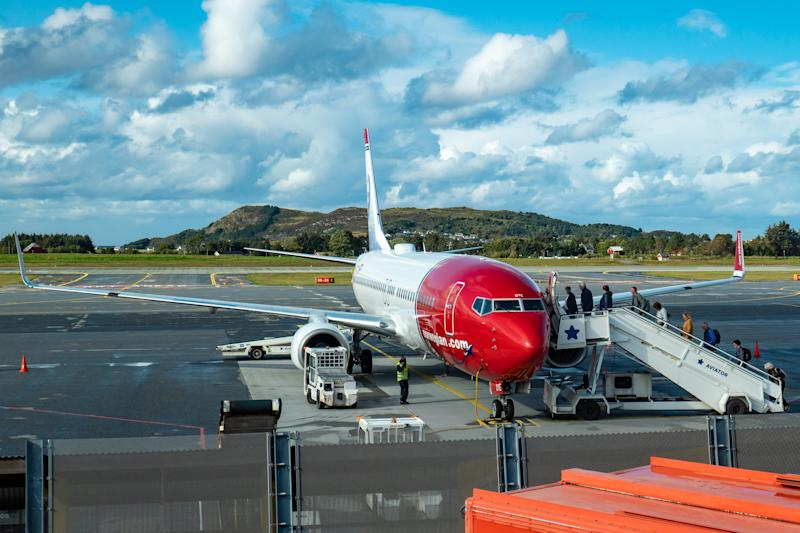Norwegian Air Shuttle Boeing 737-800 aircraft with registration LN-DYE as seen with passengers boarding on the airplane for departure at Ålesund Airport, Vigra AES ENAL in Møre og Romsdal county, Norway. Norwegian Air Shuttle DY NAX NOR is a low-cost budget airline, the third largest carrier in Europe, famous for the red nose livery and the portraits of high achievers on the tail fins of the aircraft. The airline the past days faced financial issues, struggling to pay the dept and their bondholders and shareholders, seeking now for financial survival, with the problem being intensified after the grounding of 18 of their Boeing 737 MAX. The airline connects Alesund to Oslo - Gardemoen and Alicante seasonal. (Photo by Nicolas Economou/NurPhoto via Getty Images)