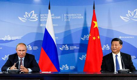 Russian President Putin and Chinese President Xi Jinping attend a meeting with participants of a round table discussion on Russia-China Cooperation on the sidelines of the Eastern Economic Forum in Vladivostok