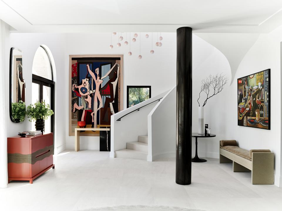 """<div class=""""caption""""> Wecselman designed Joyner's foyer to act as a mini art gallery. Pieces include a Picasso tapestry and a specially commissioned piece by Ernie Barnes. Since Joyner adores the color red, Wecselman also custom designed a cabinet for him in a vibrant shade. The pendant lights were also custom, from <a href=""""https://bocci.com/"""" rel=""""nofollow noopener"""" target=""""_blank"""" data-ylk=""""slk:Bocci"""" class=""""link rapid-noclick-resp"""">Bocci</a>. </div>"""