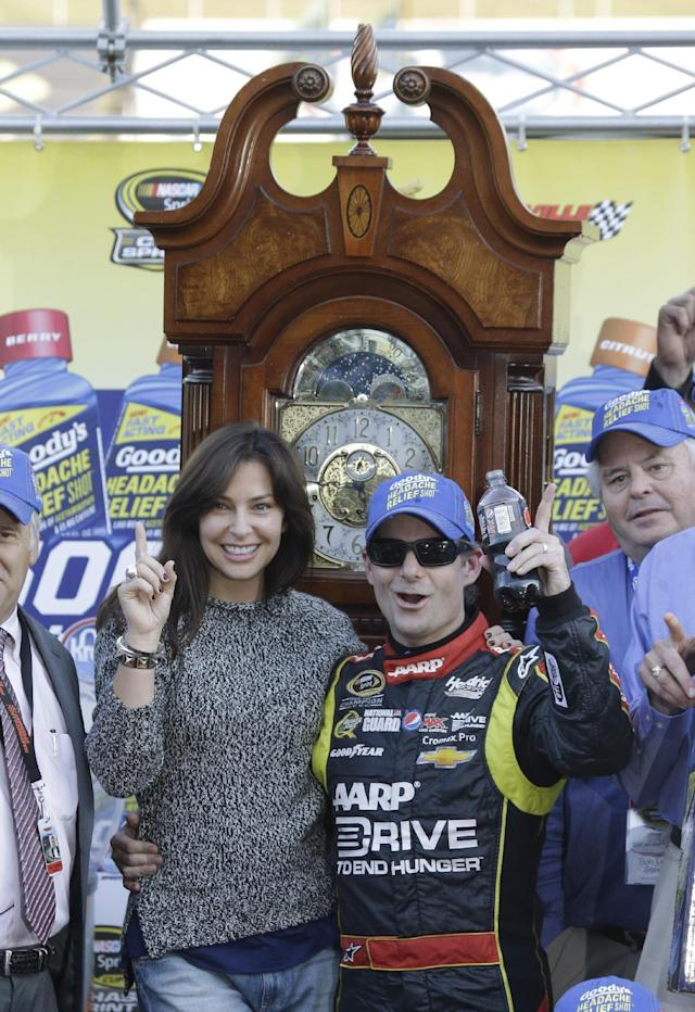 Jeff Gordon celebrates winning the NASCAR Sprint Cup auto race at Martinsville Speedway with his wife, Ingrid Vandebosch, left, in Martinsville, Va., Sunday, Oct. 27, 2013. (AP Photo/Steve Helber)