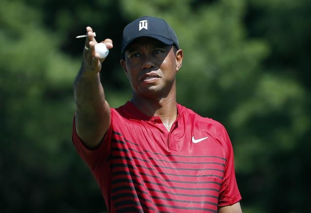 FILE - In this Monday, Sept. 3, 2018, file photo, Tiger Woods indicates the direction of the wind before teeing off on the third hole during the final round of the Dell Technologies Championship golf tournament at TPC Boston in Norton, Mass. Woods once took for granted that he would end his season at the Tour Championship. Now, just being at East Lake feels like an accomplishment. (AP Photo/Michael Dwyer, File)