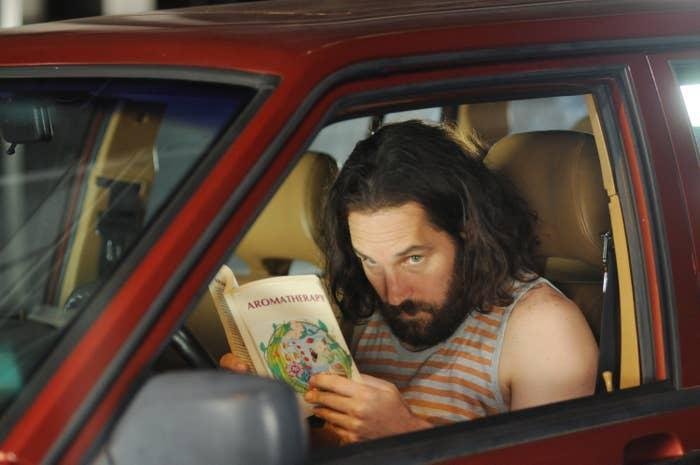 Paul Rudd reading in a car and spying on someone