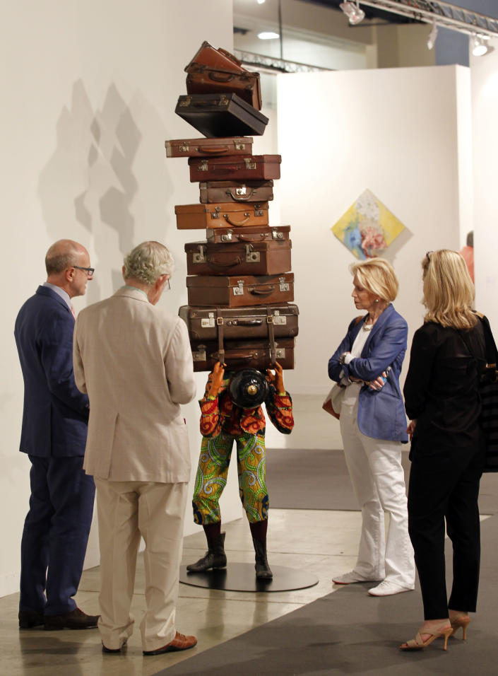 """FILE - This Dec. 5, 2012 file photo shows a crowd of people looking at a sculpture titled """"Homeless boy,"""" by Yinka Shonibare on display as part of Art Basel Miami Beach in Miami Beach, Fla. The 2013 Art Basel Miami Beach takes place Dec. 5-8. (AP Photo/Wilfredo Lee, File)"""