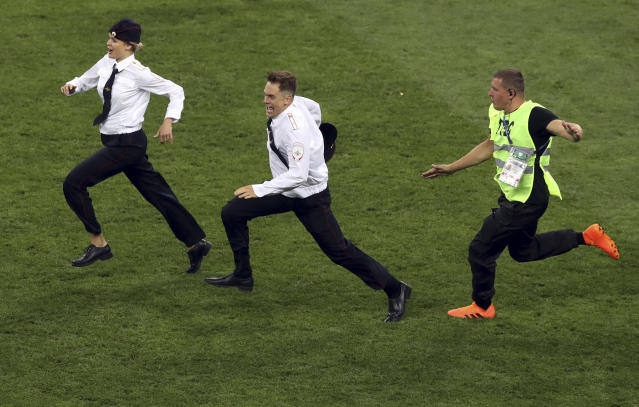 A steward runs after two people that invaded the pitch during the final match between France and Croatia at the 2018 soccer World Cup in the Luzhniki Stadium in Moscow, Russia, Sunday, July 15, 2018. (AP Photo/Thanassis Stavrakis)
