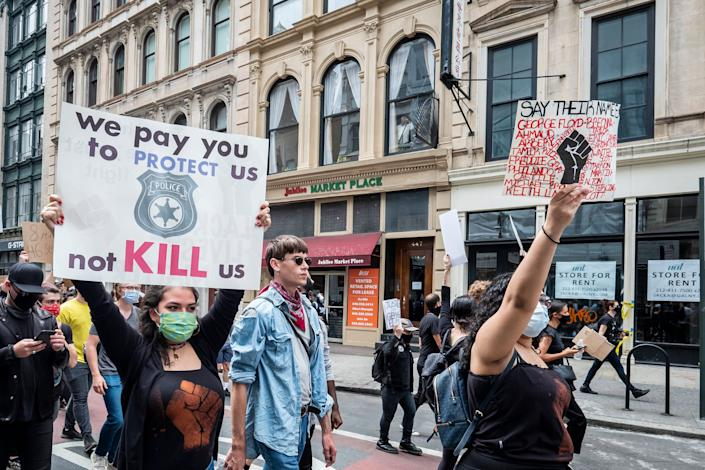"""<i>New York City demonstrators walk from Foley Square past 1 Police Plaza on their way to Washington Square Park for a peaceful moment of reflection for those killed by police. The sign on the left reads: """"We pay you to protect us, not kill us.""""</i>"""
