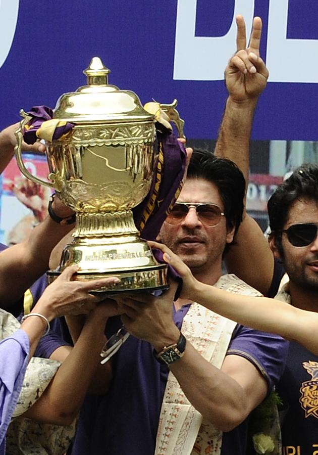 Shah Rukh Khan, owner of IPL cricket team Kolkata Knight Riders holdS up the IPL Twenty20 champion's trophy during celebrations in front of the Writers Building in Kolkata on May 29, 2012.   The Knight Riders' victory in the tournament final on May 27 was their first success in the IPL, an annual Twenty20 cricket tournament which pulls in huge audiences across India with its blend of hard-hitting cricket and Bollywood-style entertainment.  AFP PHOTO/ STR        (Photo credit should read STRDEL/AFP/GettyImages)
