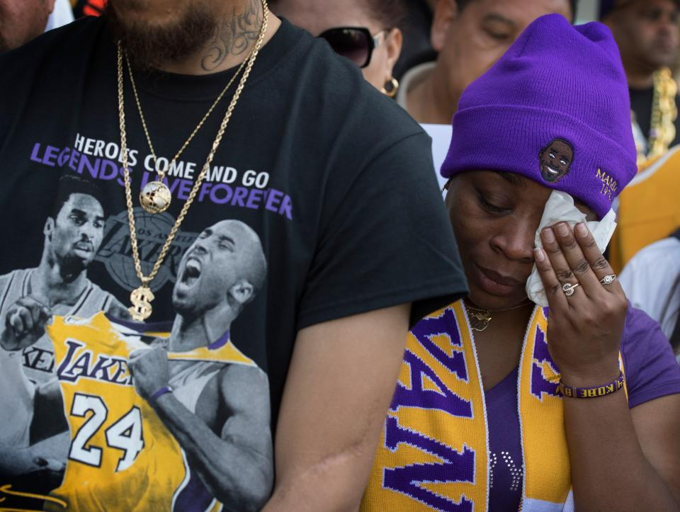 """Fans react as they watch the """"Celebration of Life for Kobe and Gianna Bryant"""" service on an mobile device outside the Staples Center in Downtown Los Angeles on February 24, 2020."""