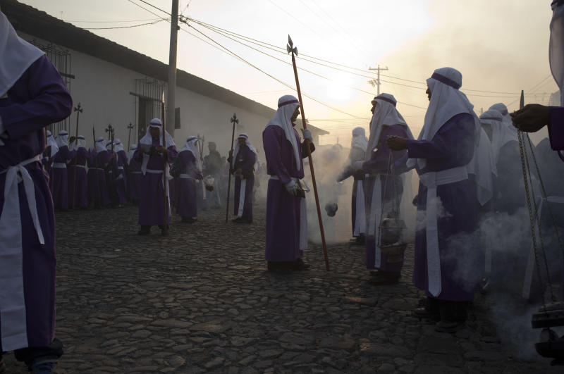 Penitents burn incense as they take part in a procession by La Merced church as part of Holy Week celebrations in Antigua Guatemala, Friday, April 18, 2014. Holy Week commemorates the last week of the earthly life of Jesus Christ culminating in his crucifixion on Good Friday and his resurrection on Easter Sunday. (AP Photo/Moises Castillo)
