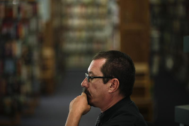 Library Branch Manager Matt Beatty works in front of book stacks at a San Diego Public Library Friday, June 8, 2012, in San Diego. Beatty has worked for the city as a librarian for more than 11 years. Voters in San Diego and San Jose overwhelmingly approved ballot measures last week to roll back municipal retirement benefits - and not just for future hires but for current employees. (AP Photo/Gregory Bull)