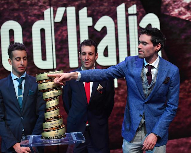 """Left to right, Italian riders Fabio Aru and Vincenzo Nibali and Dutch rider Tom Dumoulin pose for a photo near the trophy during the presentation of the """"Giro d'Italia"""", Tour of Italy, 2018 in Milan, Italy, Wednesday, Nov. 29, 2017. Four-time Tour de France champion Chris Froome says he will ride the Giro d'Italia next year in an attempt to win a third consecutive Grand Tour. (Daniel Dal Zennaro/ANSA via AP)"""
