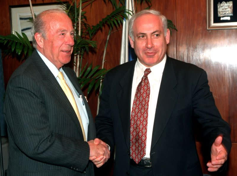 FILE PHOTO: Israeli Prime Minister Benjamin Netanyahu gestures towards the press as he shakes hands with former U.S. Secretary of State George Shultz at the start of their meeting