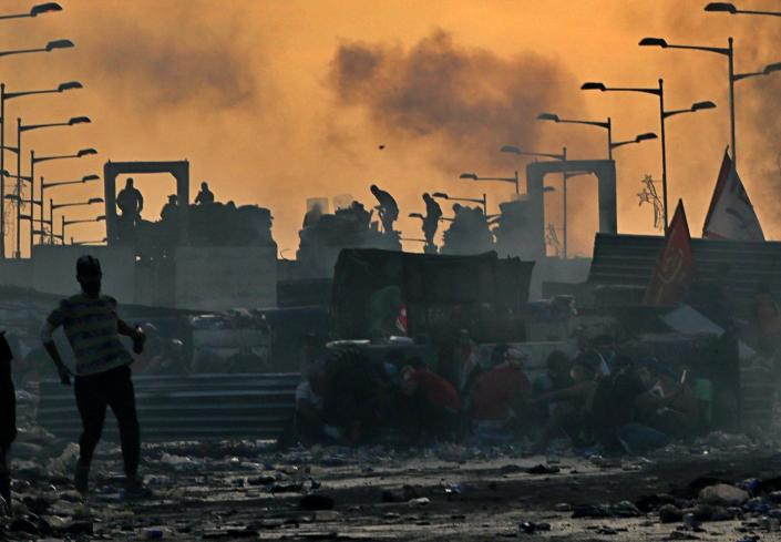Anti-government protesters take cover while Iraqi security forces, back, fire tear gas and close the bridge leading to the Green Zone, during a demonstration at sunset in Baghdad, Iraq, Sunday, Oct. 27, 2019. Protests have resumed in Iraq after a wave of anti-government protests earlier this month were violently put down. (Photo: Khalid Mohammed/AP)