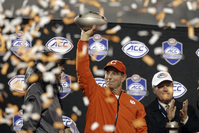 FILE - In this Saturday, Dec. 1, 2018, file photo, Clemson head coach Dabo Swinney raises the trophy after Clemson won the Atlantic Coast Conference championship NCAA college football game against Pittsburgh in Charlotte, N.C. Swinney, in his 10th year at Clemson, like most coaches is a stickler for hard work. But he also is keen on celebrating success. (AP Photo/Chuck Burton, File)