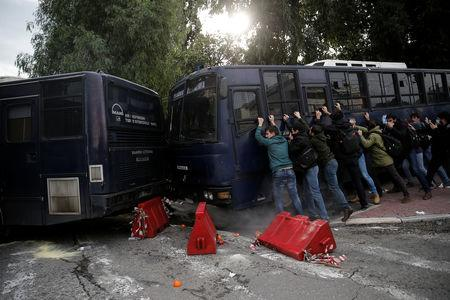Protesters push a police bus as Greek school teachers scuffle with riot police during a demonstration against government plans to change hiring procedures in the public sector in Athens, Greece, January 11, 2019. REUTERS/Costas Baltas