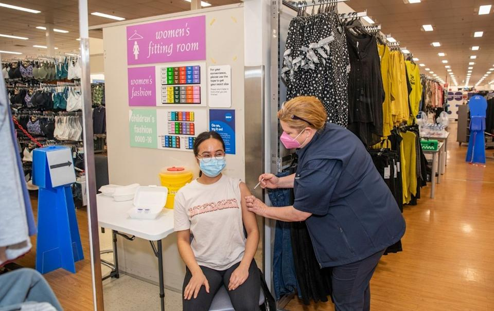A woman receives a vaccine at a Big W vaccination centre. Source: Woolworths Group