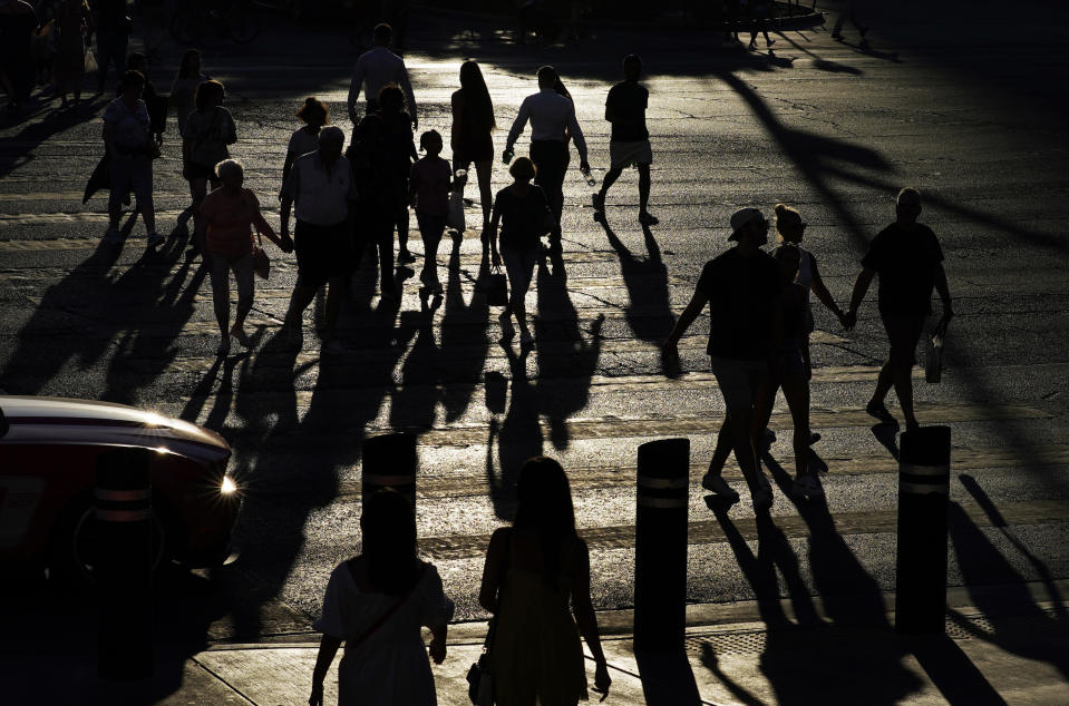 People cross Las Vegas Boulevard, Friday, July 2, 2021, in Las Vegas. Tourists are streaming into the city again, and gambling revenue has hit an all-time high. But that progress is threatened: Nevada this week saw the highest rate of new COVID-19 cases in the country. (AP Photo/John Locher)