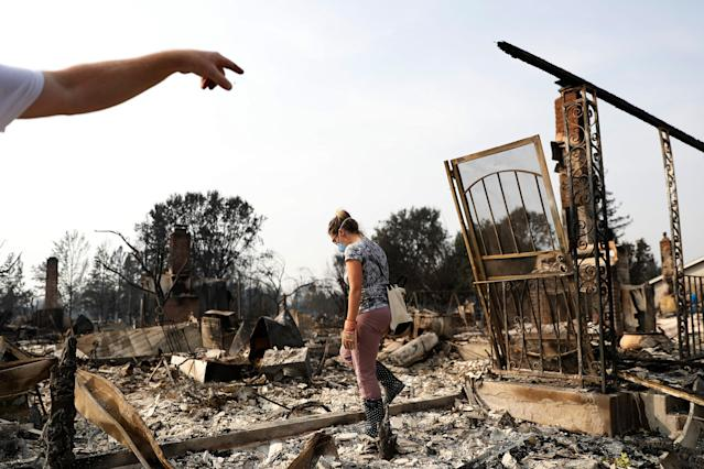 <p>Harper Bishop (L) points to a section of his home as wife Cristy surveys their home destroyed by the Tubbs Fire in Santa Rosa, Calif., Oct. 10, 2017. (Photo: Stephen Lam/Reuters) </p>