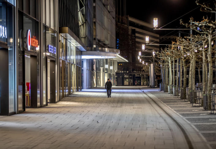 A man walks through the empty shopping street in Frankfurt, Germany, Friday, Feb. 12, 2021. Germany authorities extended the country's partial lockdown for another four weeks to battle the coronavirus pandemic. (AP Photo/Michael Probst)