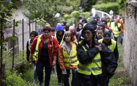 <span>A group of citizens walks before taking part in a research operation, seven days after Maelys, 9, was reported missing on September 2</span> <span>Credit: PHILIPPE DESMAZES/AFP </span>