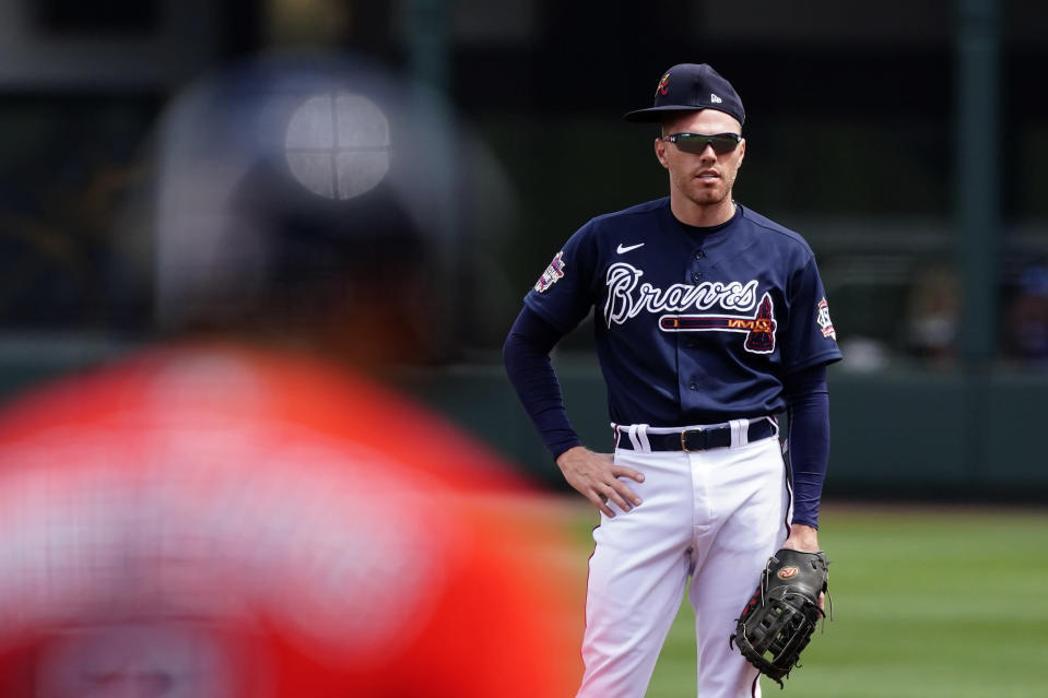 Atlanta Braves first baseman Freddie Freeman wears his hat sideways as he waits for Boston Red Sox' Xander Bogaerts (2) to bat during the first inning of a spring training baseball game on Tuesday, March 23, 2021, in North Port, Fla. (AP Photo/John Bazemore)