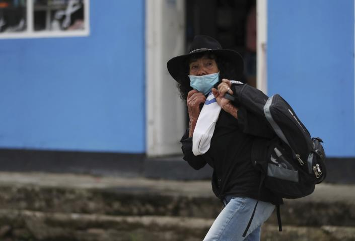 Wearing a mask to curb the spread of the new coronavirus, a woman walks in Campohermoso, Colombia, Thursday, March 18, 2021. According to the Health Ministry, Campohermoso is one of two municipalities in Colombia that has not had a single case of COVID-19 since the pandemic started one year ago. (AP Photo/Fernando Vergara)