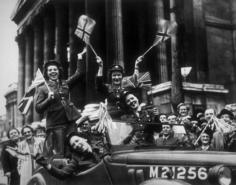 <p>Members of the Women's Royal Army Corps wave the Union Jack flag as they drive their service jeep through the streets of London. </p>