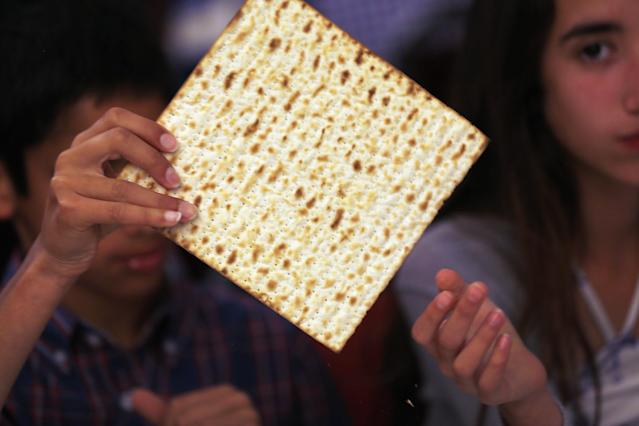 MIAMI BEACH, FL - MARCH 25: Omri Brandes (L) and Nitzan Brandes eat matzo during a community Passover Seder at Beth Israel synagogue on March 25, 2013 in Miami Beach, Florida. The community Passover Seder that served around 150 people has been held for the past 30 years and is welcome to anyone in the community that wants to commemorate the emancipation of the Israelites from slavery in ancient Egypt. (Photo by Joe Raedle/Getty Images)