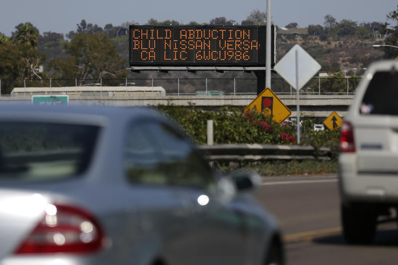 Drivers pass a display showing an Amber Alert, asking motorists to be on the lookout for a specific vehicle Tuesday, Aug. 6, 2013, in San Diego. The husband of a woman whose body was found in a burned house near the U.S.-Mexico border said Tuesday that he knew the man suspected of killing his wife and abducting one or both of their children. (AP Photo/Gregory Bull)