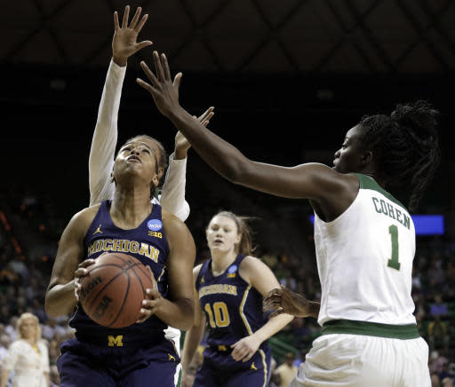 Michigan guard Akienreh Johnson (14) positions for a shot attempt as Baylor's Juicy Landrum, rear, and Dekeiya Cohen (1) defends in the first half of a second-round game at the NCAA women's college basketball tournament in Waco, Texas, Sunday, March 18, 2018. (AP Photo/Tony Gutierrez)