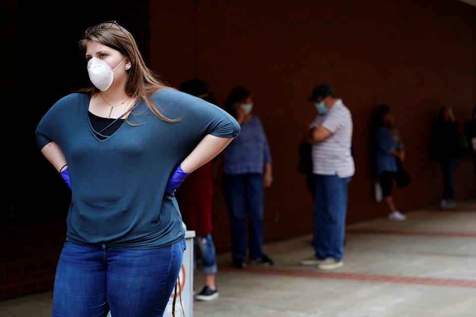 A woman who lost her job waits in line to file for unemployment following an outbreak of the coronavirus disease (COVID-19), at an Arkansas Workforce Center in Fort Smith, Arkansas, U.S. April 6, 2020. REUTERS/Nick Oxford
